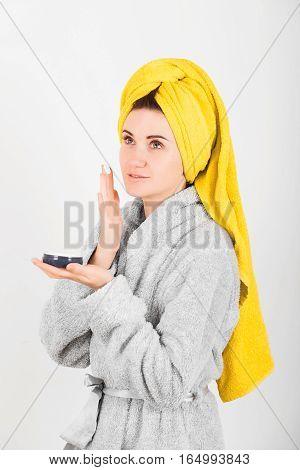 Cute woman in grey bathrobe with yellow towel on head