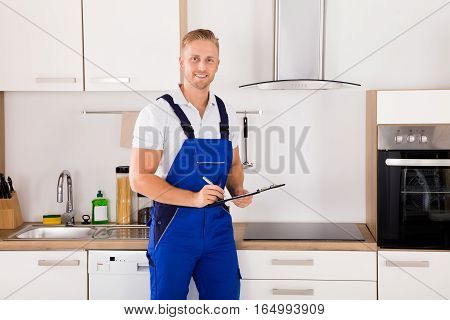 Portrait Of A Happy Male Technician With Clipboard In Kitchen