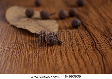 The granules of pepper on wood background