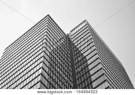 Corner of a glass building against a foggy sky