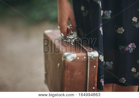 girl in a vintage dress holding a vintage suitcase