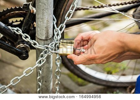 Close-up Photo Of Person's Hand Lockpicking Bicycle Padlock