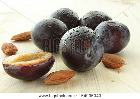 Five plum with pips and drops on the wooden board.
