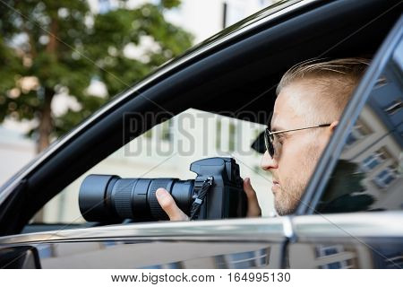Man Doing Surveillance Sitting Inside Car Photographing With SLR Camera