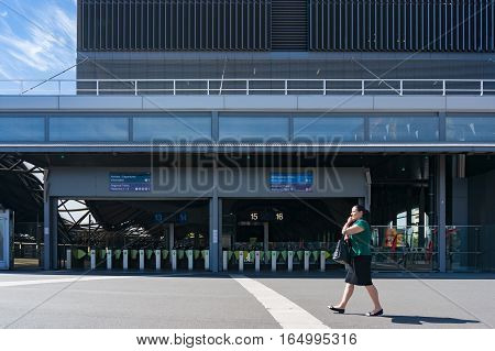 Southern Cross Station Entrance With Pay Gates And Woman Walking And Talking Phone