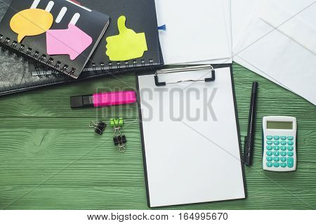 Workplace with folder with a blank sheet of paper notepads and other office supply on a desk with copy space top view. Blank template for design mock-up. Office desk flat lay.