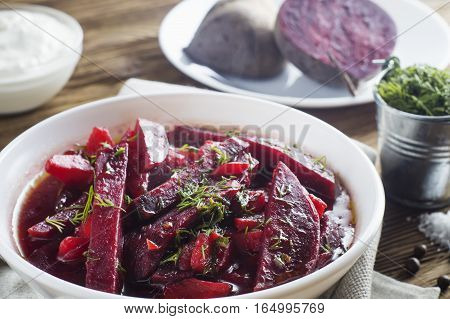 Vegetable soup - red borsch in a white bowl on a rustic wooden background clouse up. Healthy beetroot soup vegetarian food. Delicious beet soup with sour cream.