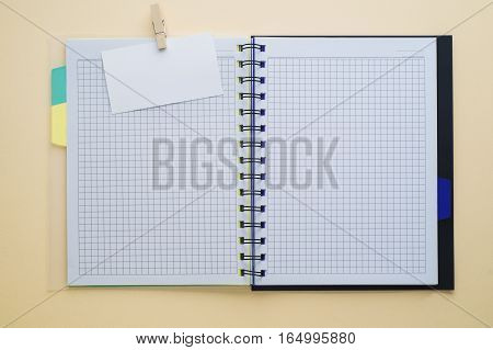 Open sketchbook or scrapbook with blank white business card mock up template. Empty white notebook on wooden table flat lay. Top view.