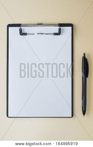 Blank paper on black clipboard with copy space on beige background vertical photo. Folder with blank paper design mockup. Document holder mock up template.