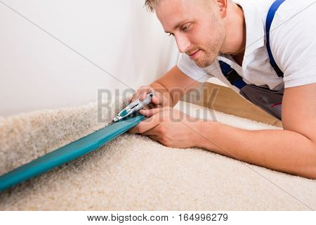 Close-up Of A Young Handyman Fitting Carpet While Installation With Cutter