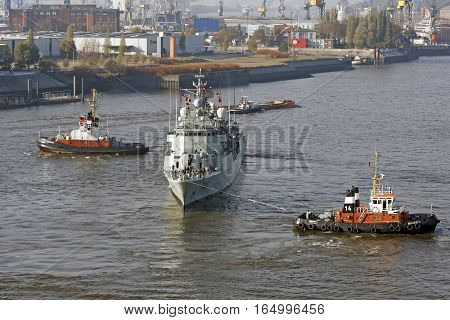 HAMBURG GERMANY - NOVEMBER 14: In Harbor help two tugs to reverse the direction of sailing one large military vessel in Hamburg Germany on November 14 2016
