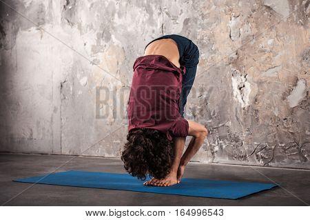 Man doing yoga or pilates exercise. Uttanasana head to knees pose. Full length photo