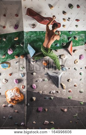 Muscular and fit topless man exercise bouldering and climbing indoor at artificial wall