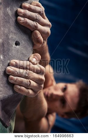 Closeup of man's hands on handhold on artificial climbing wall hand in focus