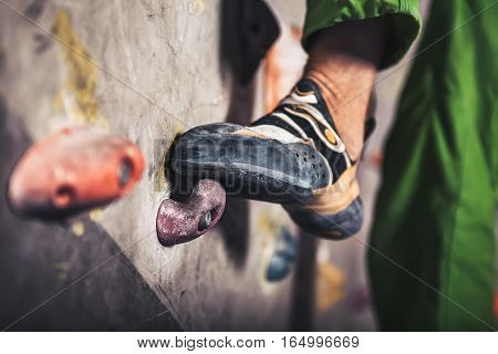 Close-up image of male foot on climbing wall