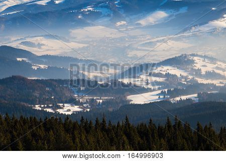 Winter mountain landscape - top view of snow mist covered valley in the background of mountain peaks. Ski resort Kubinska Hola; Western Tatras. Slovakia. Travel destination for winter vacations and skiing.