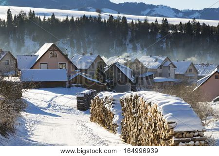 Winter rural landscape - mountain village covered with snow misty morning. Western Tatras. Slovakia. Orava region. Travel destination for winter vacations and skiing.