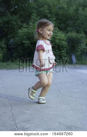 Little girl running. Happy girl 2-3-4 years old with braids running down the road in the park in the evening