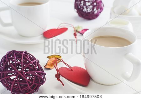Romantic breakfast with couple white cups of coffee on white wooden background. Valentine's day celebration concept with hearts and cups. Cocoa or coffee with milk with marshmallow clouse up.