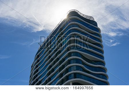 Skyscraper building with curvy organic forms against blue sky and sun on the background. Contemporary architecture on sunny day Melbourne city modern architecture and urban environment concept poster