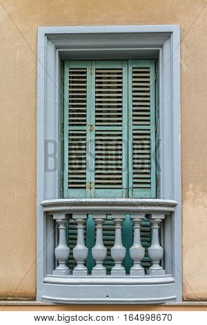 An old green window set on a plaster wall