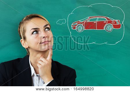 Young Beautiful Businesswoman Thinking To Buy A Car Against Blackboard