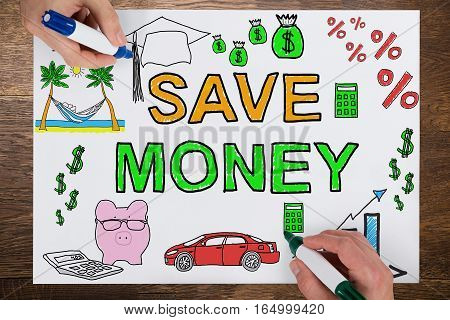 Close-up Of Two Businesspeople Drawing Save Money Concept On White Paper Using Colorful Marker On Wooden Desk