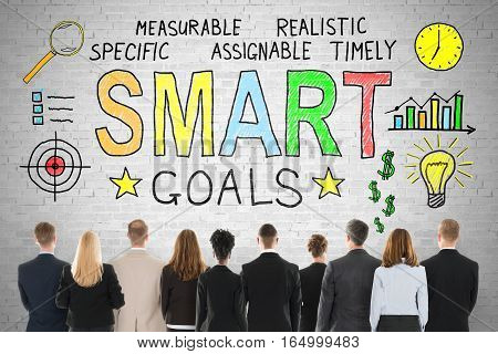 Rear View Of Businesspeople Looking At Smart Goals Concept On Brick Wall