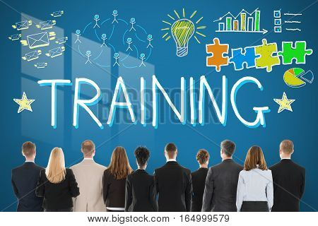 Rear View Of Businesspeople Looking At Training Concept Drawn On Blue Wall