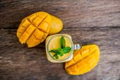 Mango smoothie in a glass Mason jar and mango on the old wooden background. Mango shake. Tropical fruit concept. poster