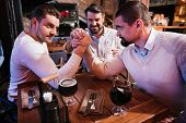 Who is stronger. Good looking strong male friends sitting opposite each other and arm wrestling while deciding who is stronger. poster
