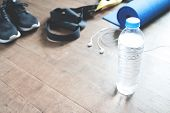 Fitness concept with bottle of water sneakers TRX yoga mat and earphones on wood floor Copy space poster