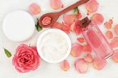 Skincare beauty treatment plant-based products with wink rose petals. Jar of body moisturizer, attar bottle toning lotion, top view homemade cosmetic ingredients. poster
