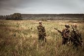 Hunters in camouflage walking through rural field during hunting season season in overcast day with moody sky poster