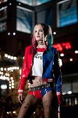 Cosplayer girl in costume Harley on background lights of night city. Cosplay poster