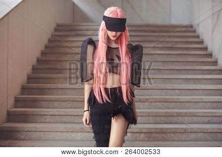 Japan anime cosplay. Colorful portrait of young attractive asian woman in sexy dress with creative make-up and wearing pink wig outdoors. Trendy Japanese girl walking outside on city street. Cool fashion look poster