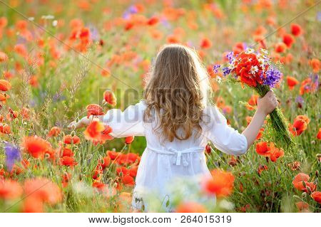 Adorable Little Girl With Wild Field Flowers Running Thru Meadow In Summer Poppy Field