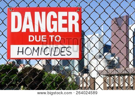 Sign Danger Due To Homicides Attached On The Fence In The Front Of The Town