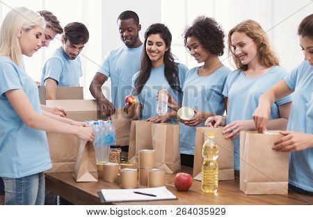 Donation. Volunteers Packing Food And Drinks Into Paper Bags, Serving Nutrition For Homeless, Copy S