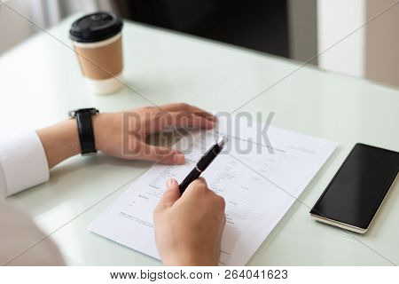 Close-up Of Male Hands Filling In Application Form In Office. Caucasian Businessman Sitting At Table