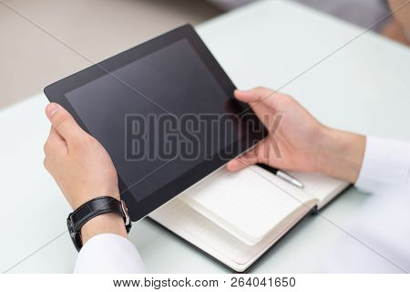 Close-up Of Male Hands Using Digital Tablet In Office. Young Caucasian Businessman Or Student Sittin
