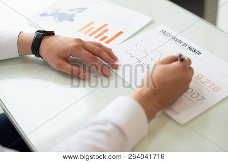 Close-up Of Male Hands Writing On Paper With Graph Sale. Caucasian Businessman Sitting At Table And