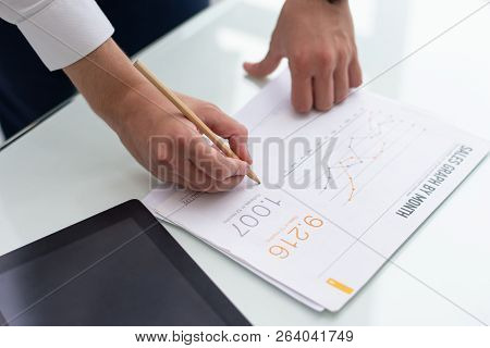Close-up Of Male Hands Writing On Sales Report In Office. Young Caucasian Businessman Standing At Ta