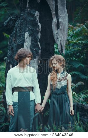 Sad young couple of elves in magical forest agaistdying burned-down tree outdoor on nature. Fairy tale, nature disaster and magik people concept. poster