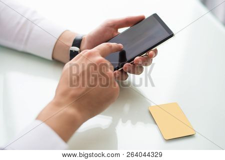 Close-up Of Unrecognizable Man Browsing Internet On Smartphone While Searching For Information. Busi