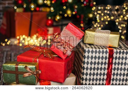 Close Up Christmas Gift Box. Christmas Presents In Red And Brown Boxes On Christmas Tree Background