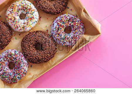 Delicious Glazed Donuts In Box On Pink Surface. Flat Lay Minimalist Food Art Background. Top View.
