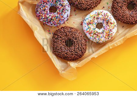 Delicious Glazed Donuts In Box On Yellow Surface. Flat Lay Minimalist Food Art Background. Top View.
