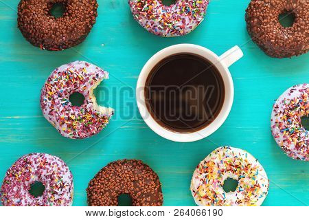 Delicious Glazed Donuts And Cup Of Coffee On Turquoise Surface. Flat Lay Minimalist Food Art Backgro