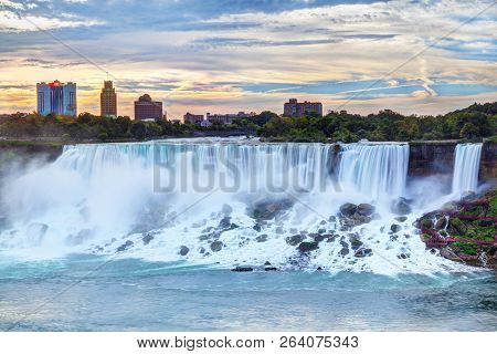 Sunrise Over American Falls And Bridal Veil Falls At Niagara Falls, New York State, Usa, With Citysc